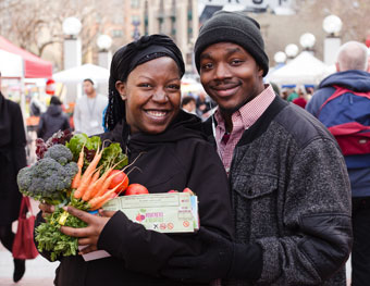 A couple holding vegetables at a farmer's market